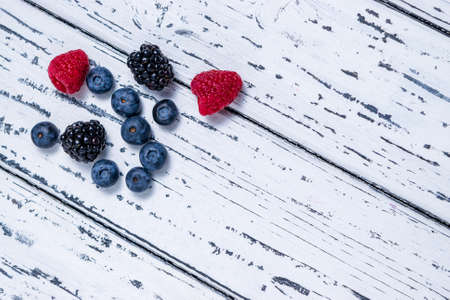 Raspberries, blackberries and blueberries on an old white wooden background. Flat lay. Healthy food concept.