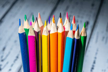 Set of colorful pencils on the wooden background .