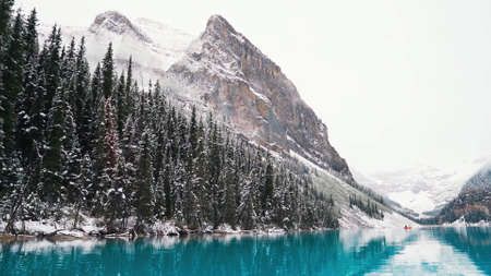 Blue lake and mountains. First snow Morning at Moraine Lake in Banff National Park Alberta Canada Snow-covered winter mountain lake in a winter atmosphere. Beautiful background photo. Standard-Bild