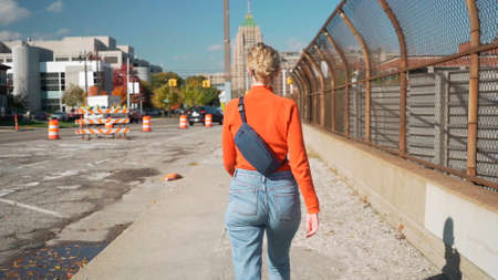 Girl on a walk. A girl in jeans walks along the street. Photo from the back. Rear view of young woman.