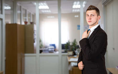 Funny young male businessman inside office background.  One person, dressed according to business dress code, located inside the office interior