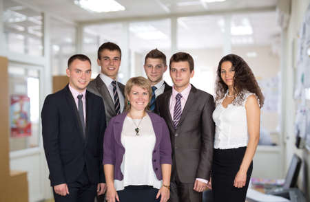 Friendly harmonious business team.  Six people dressed in line with business dress code enjoy working together in the open space office Stock Photo