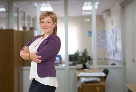dress code: Mature female businesswoman at the office.  One person, dressed according to business dress code, located inside the office interior