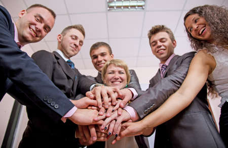but: Friendly harmonious business team. Six business people join hands and smiling. Focus is on hands, but face expression is recognisable Stock Photo