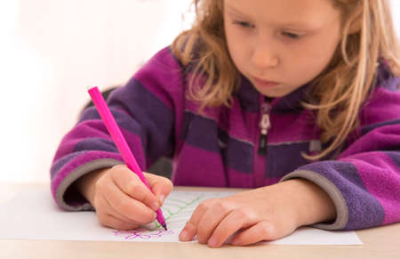 absorbed: Child draws the picture with color pen. Serious, absorbed face Stock Photo