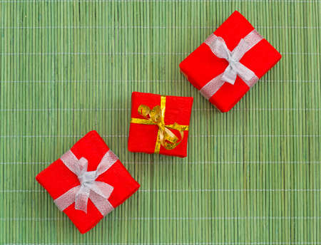 Three decoratively packed gifts on the green bamboo mat photo