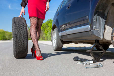 pantyhose: Leggy female changing wheel of car. Lady dressed in provocative clubbing pantyhose and bright red shoes high heels mini skirt rolls large wheel to car fixed on jackscrew with some tools Stock Photo