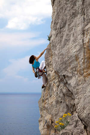 hangs: Female climber climbs wall in over the sea. Female extreme climber hangs on her hand on the natural rock. Sea and sky on the background Stock Photo