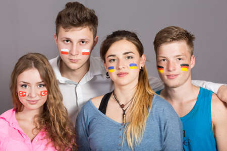 rooting: Four teenagers with flags drawn on the faces. Soccer fans with different country flags painted on faces Stock Photo