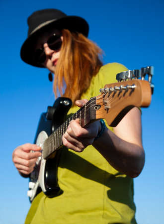 wearer: Stylish female musician with red hairs wearer in black hat and green shirt plays on the guitar. Deep blue sky on the background. Focus on the guitar face is blurred