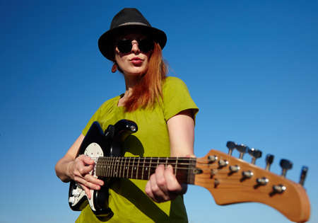 wearer: Stylish female musician with red hairs wearer in black hat and green shirt plays on the guitar. Deep blue sky on the background. Focus on the face