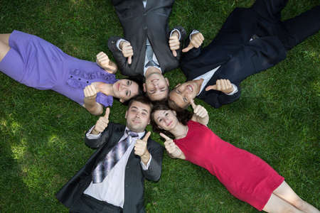 Lunch break. Five business people are relaxing on the glade of grass during lunch time. Happy faces