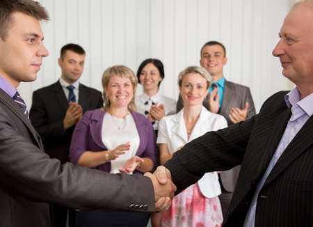 Business award Mature businessman congratulates younger employee standing in front of the happy team
