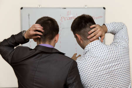 team communication: Two male corporate workers realise that they did a mistake