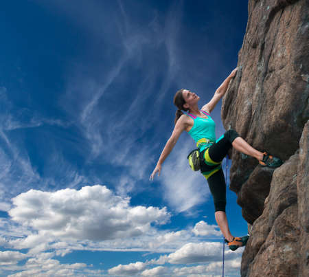 crack climbing: Female rock climber hanging over the abyss Brave and confident female rock climber enjoys hanging on her hand over the deep abyss