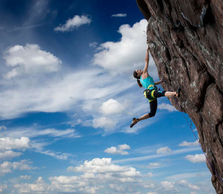 Female rock climber hanging over the abyss Brave and confident female rock climber enjoys hanging on her hand over the deep abyss