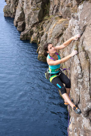 crack climb: Brave and confident female rock climber enjoys hanging on her hands over the deep water abyss Stock Photo