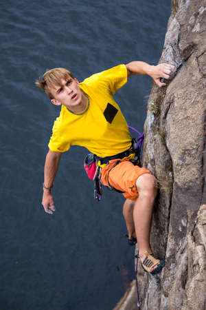 overhang: Young male rock climber hanging over the water making his next difficult move. Serious manful face Stock Photo