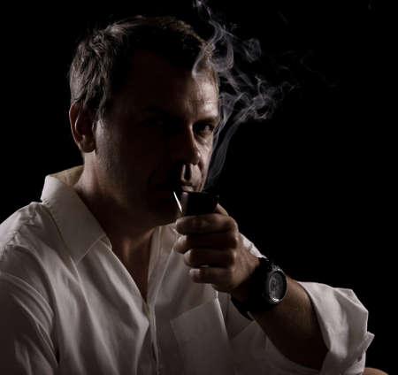 Portrait of pipe smoker man smoking vintage tobacco pipe on black background Stock Photo