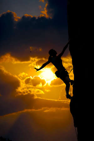 sport silhouette: Elegant female alpine climber ascents natural rock against impressive sunset