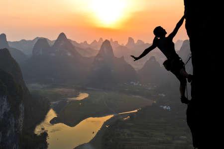 Elegante silueta escalador extrema femenina contra la puesta de sol sobre el río. China, el paisaje típico chino con montañas y el río
