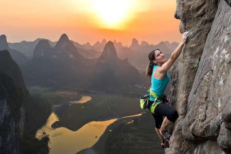 Escalador extremo femenino vence roca escarpada en contra de la puesta de sol sobre el río. China, el paisaje típico chino con montañas y el río