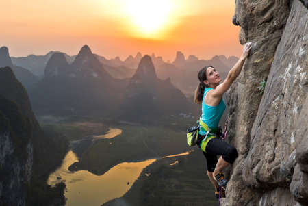 Female extreme climber conquers steep rock against the sunset over the river. China typical Chinese landscape with mountains and river Foto de archivo