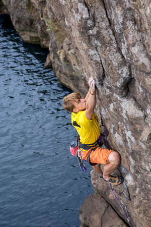 manful: Young male rock climber hanging over the water and making his next difficult move. Serious manful face