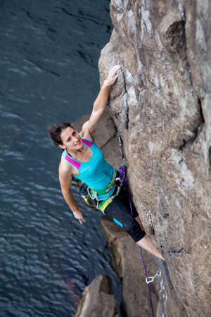 crack climbing: Brave and confident female rock climber enjoys hanging on her hands over the deep water abyss. She is looking ahead planning her next move