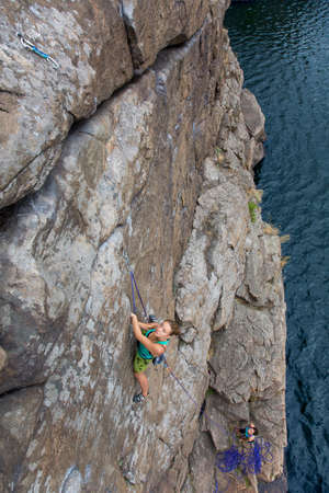 belaying: Two young female extreme climbers climb the rock. One is leading another is belaying. Rocky beach river natural rock outdoor summer Stock Photo