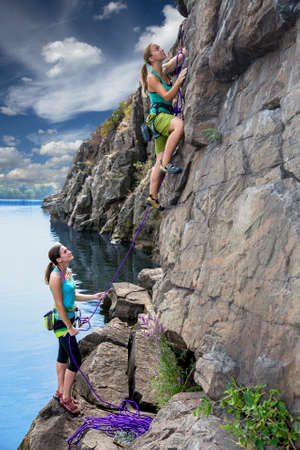 Two young female extreme climbers climb the rock. One is leading another is belaying. Rocky beach river natural rock outdoor summer 스톡 콘텐츠