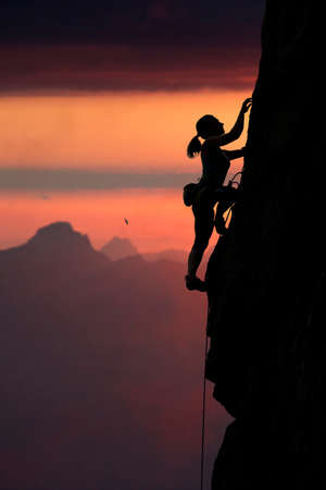 Elegant female extreme climbers silhouette against the red sunset over the mountain landscape