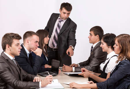 manager team: Energetic corporate manager instructs his team six people sit around the table covered by paperwork Stock Photo