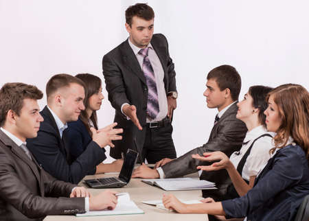 instructs: Energetic corporate manager instructs his team six people sit around the table covered by paperwork Stock Photo