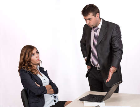 criticising: Female office employee caught by manager at inappropriate social networking during working hours Boss is criticising her pointing the laptop Stock Photo