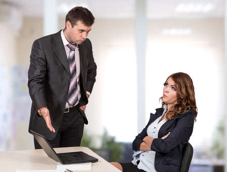 inappropriate: Female office employee caught by manager at inappropriate social networking during working hours Boss is criticising her pointing the laptop Stock Photo