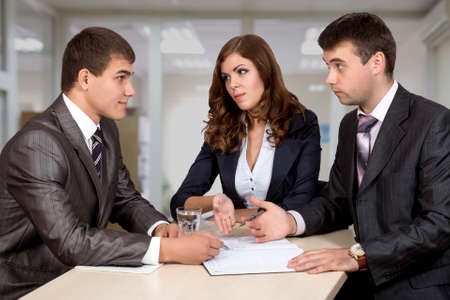 Group of three business people, male and female, discussing the deal. Office interior, serious, authentic emotions