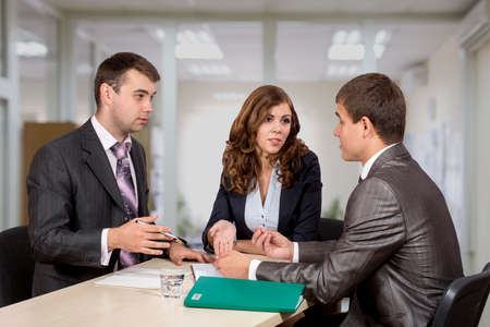 salespeople: Group of three business people, male and female, discussing the deal. Office interior, serious, authentic emotions