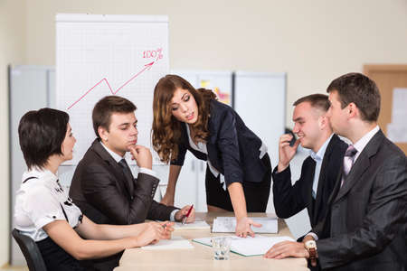 Female manager energetically talks to her team. Four people sit around the table covered by paperwork. Flip chart and open space office on the background Stock Photo