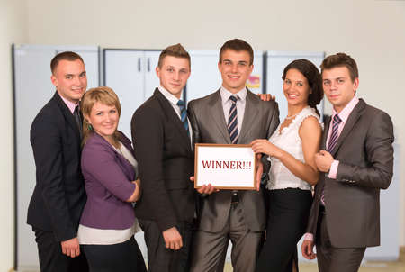 dress code: Winning corporate business team group people dressed according to business dress code keep awarding certificate with WINNER sign