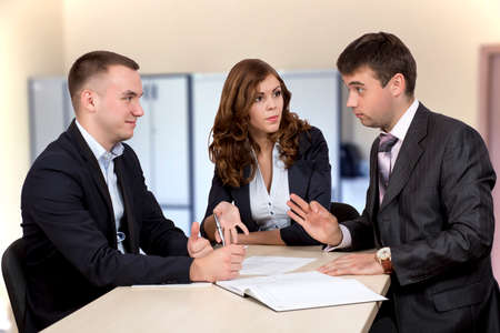 negotiation business: Business negotiations Group of three business people, male and female, discussing the deal. Office interior, serious, authentic emotions Stock Photo