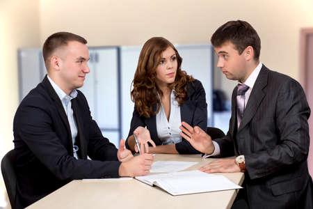negociacion: Negociaciones del asunto Grupo de tres hombres de negocios, hombres y mujeres, en discusiones sobre el acuerdo. Interior de la oficina, graves, emociones auténticas Foto de archivo