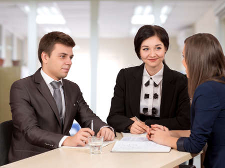 salespeople: Business negotiations Group of three business people, male and female, discussing the deal. Office interior, serious, authentic emotions Stock Photo