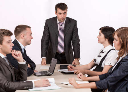 associates: Severe corporate manager is observing his business team Dissatisfied manager stays at table with group of his associates Stock Photo