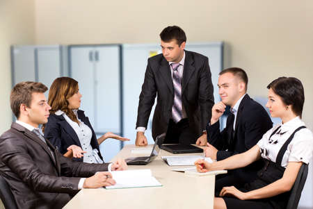 manager team: Tough meeting manager critically talks to his team group of young business people around table office interior Stock Photo