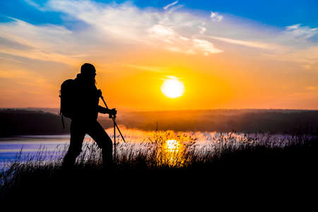 Walking female hiker silhouette and impressive colorful sunrise on the background outdoor morning water river sky sunlight Standard-Bild