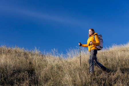 Weibliche Wanderer geht bergab und genießt warmen Sonnenlicht Verwendung Trekkingstöcke, in Daunenjacke und Trekkinghose gekleidet