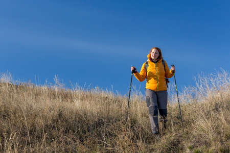 pants down: Female hiker walks downhill and enjoys warm sunlight use trekking poles, dressed in down jacket and trekking pants