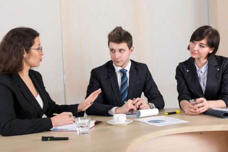disagreed: Bored, disagreed female boss and male businessman who tries to convince her. Office interior, conference table, window on the background