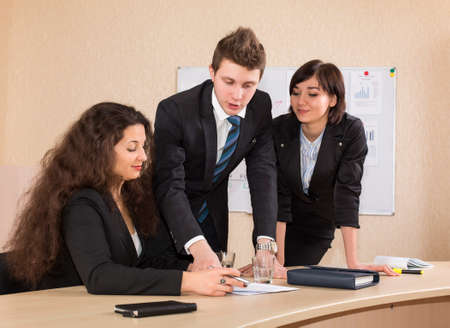 facilitate: Hot discussion about financial impact of the project Multi-ethnic business team have a discussion. Two nice females and one handsome male Stock Photo